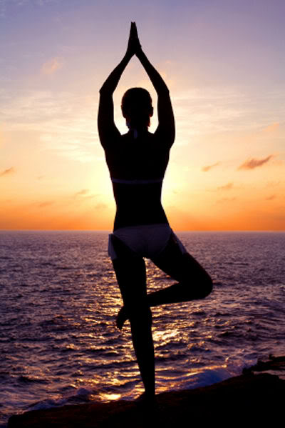 A silhouette of a woman facing the sunset in a meditative pose